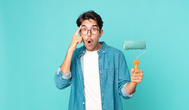 Молодой латиноамериканец выглядит удивленным, осознает новую мысль, идею или концепцию и держит малярный валик