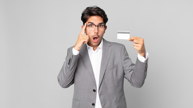 Young hispanic man looking surprised, realizing a new thought, idea or concept and holding a credit card