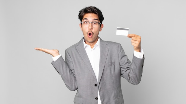 Young hispanic man looking surprised and shocked, with jaw dropped holding an object and holding a credit card