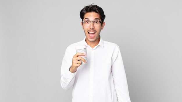 非常にショックを受けたり驚いたりして、持ち帰り用のコーヒーを持っている若いヒスパニック系男性