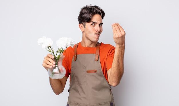 若いヒスパニック系の男性が、お金を払うように言って、身振りやお金のジェスチャーをします。花屋のコンセプト