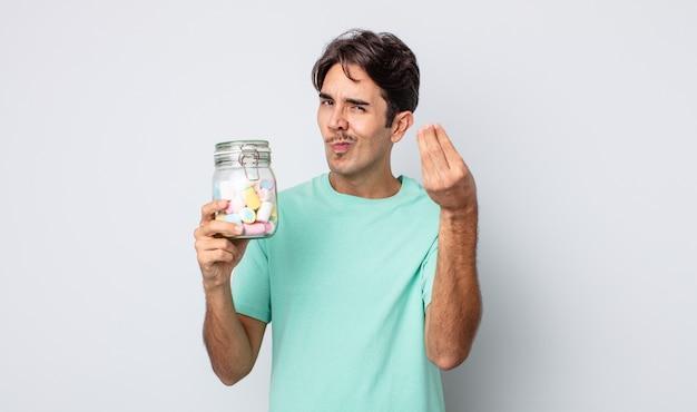 ヒスパニック系の若い男性が、お金を払うように言って、身振りやお金のジェスチャーをします。ゼリーキャンディーのコンセプト