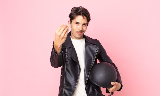ヒスパニック系の若い男性が、お金を払うように言って、身振りやお金のジェスチャーをします。バイクライダーのコンセプト