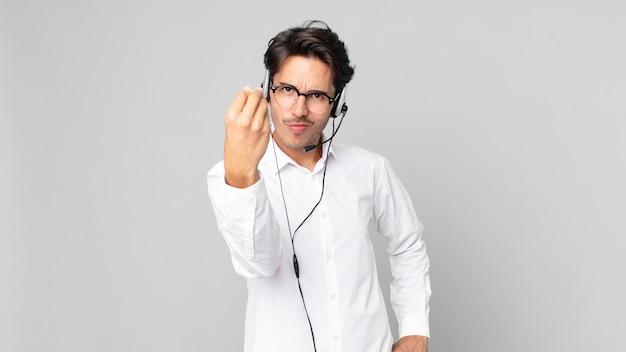 ヒスパニック系の若い男性が、お金を払うように言って、身振りやお金のジェスチャーをします。テレマーケティングの概念