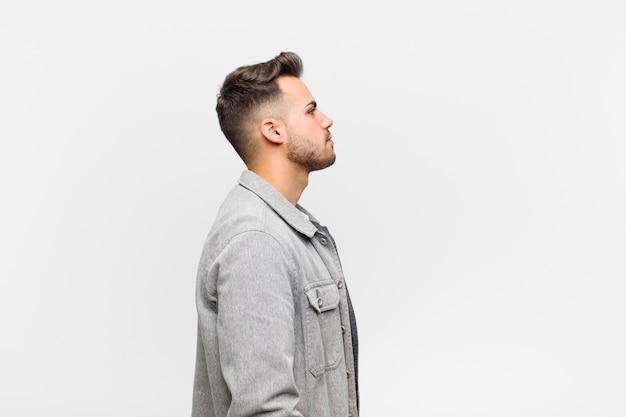 前方のスペースをコピーしようとして、灰色の壁に考えて、想像して、または空想にふける縦断ビューの若いヒスパニック男