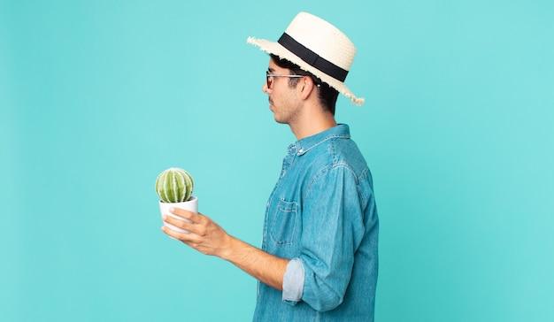 サボテンを考え、想像し、空想し、保持しているプロファイルビューの若いヒスパニック系男性