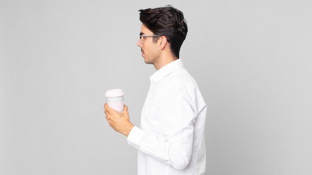プロフィールビューで若いヒスパニック系の男性が考え、想像し、空想にふけり、持ち帰り用のコーヒーを持っています