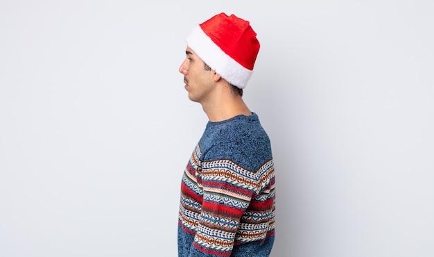 プロフィールビューの若いヒスパニック系の男性は、思考、想像、または空想にふけっています。新年とクリスマスのコンセプト