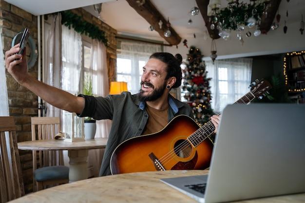 노트북으로 집에서 기타를 연주하는 젊은 히스패닉 남자. 사람들이 취미 기술 개념