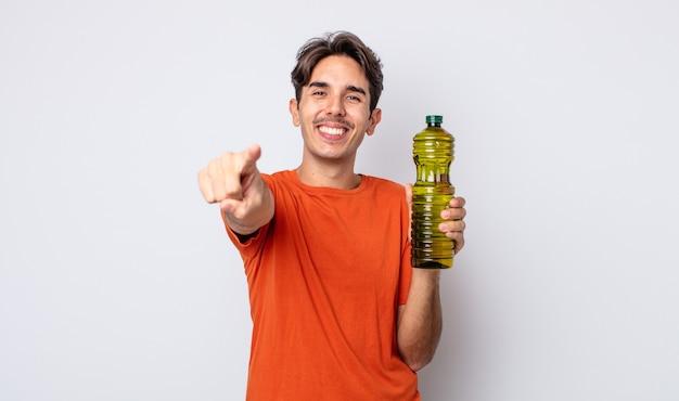 あなたを選ぶカメラを指している若いヒスパニック系の男性。オリーブオイルの概念