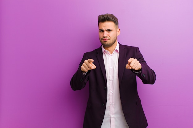 Young hispanic man pointing forward at camera with both fingers and angry expression, telling you to do your duty
