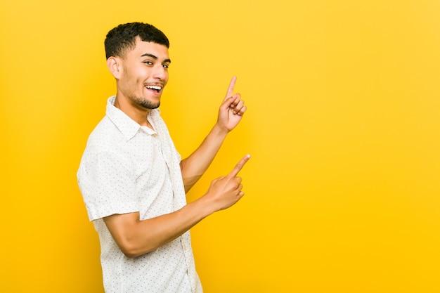 Молодой латиноамериканец, указывая указательными пальцами
