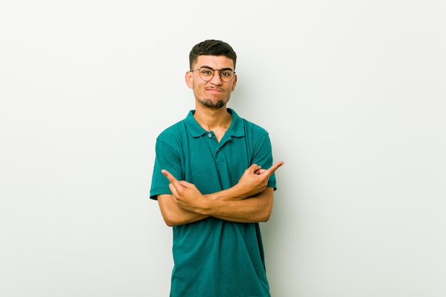 Young hispanic man points sideways, is trying to choose between two options.