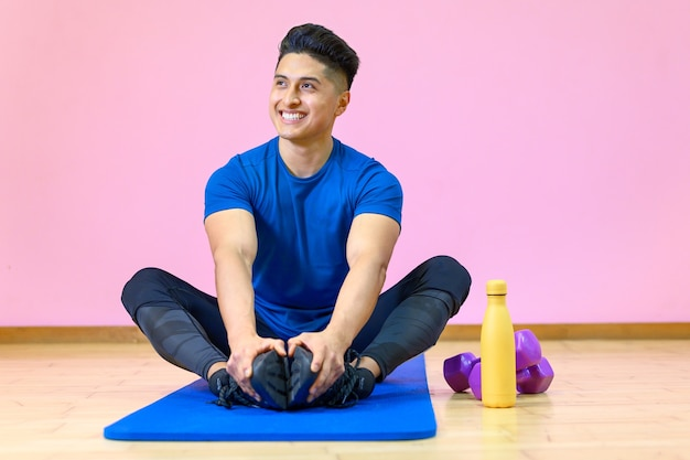 Young hispanic man practicing yoga on his mat at gym on pink background.