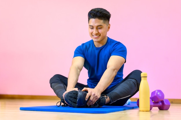 Молодой латиноамериканец упражнениями йоги на циновке в тренажерном зале на розовом фоне.