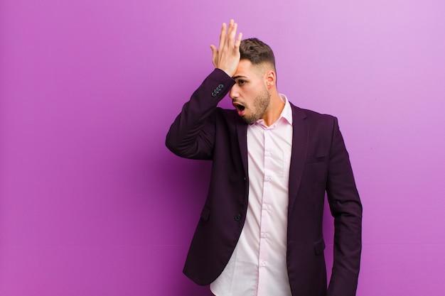 Молодой латиноамериканский мужчина поднимает ладонь ко лбу, думая, что ой, совершив глупую ошибку или вспомнив, чувствуя себя тупым