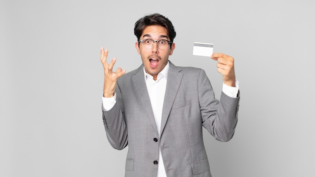 Young hispanic man screaming with hands up in the air and holding a credit card