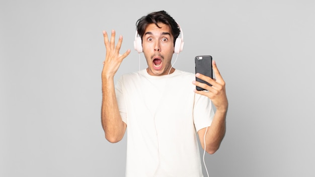 Young hispanic man screaming with hands up in the air with headphones and smartphone