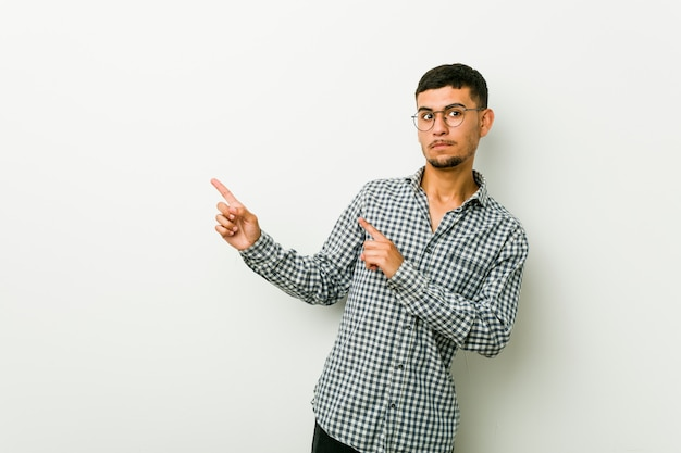 Young hispanic man shocked pointing with index fingers to a copy space.