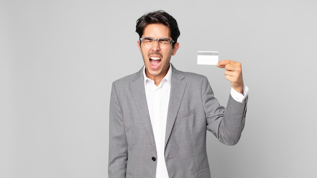 Young hispanic man shouting aggressively, looking very angry and holding a credit card