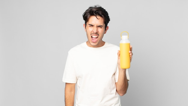 コーヒーの魔法瓶に非常に怒っているように見える、積極的に叫んでいる若いヒスパニック系の男性