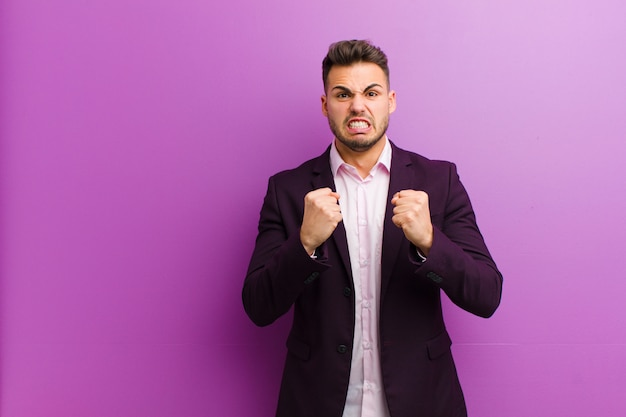 Young hispanic man shouting aggressively with annoyed, frustrated, angry look and tight fists, feeling furious