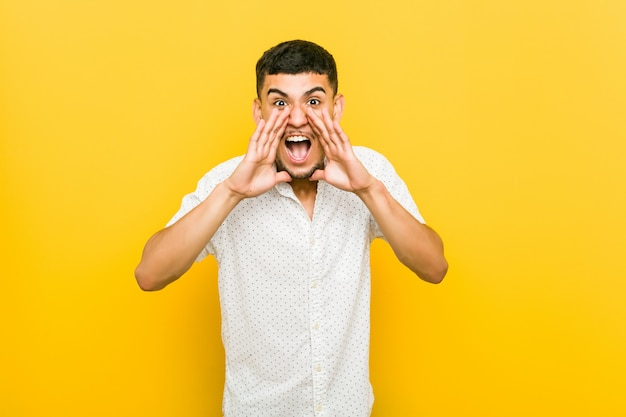 Young hispanic man shouting excited to front.