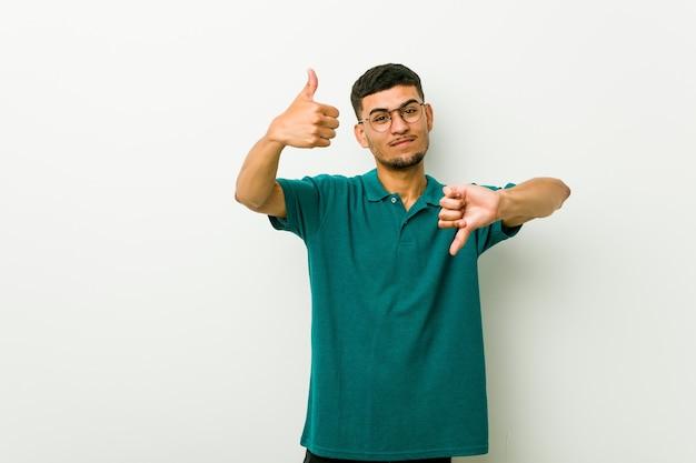 Молодой латиноамериканец показывает палец вверх и палец вниз, сложно выбрать концепцию