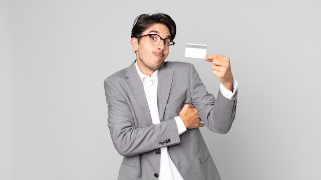 젊은 히스패닉 남자가 어깨를 으쓱하고 혼란스럽고 불확실하다고 느끼며 신용 카드를 들고 있다