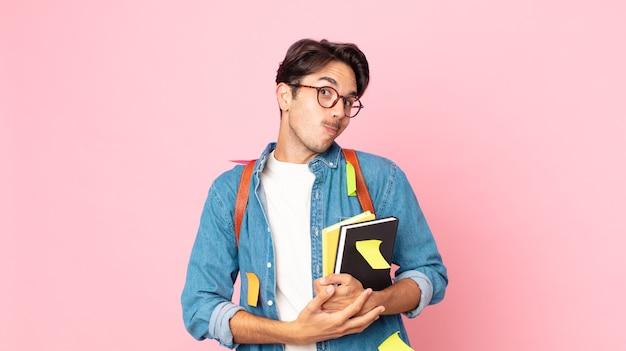 若いヒスパニック系の男性が肩をすくめ、混乱し、不安を感じています。学生の概念