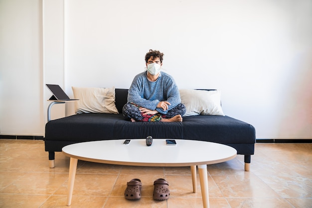 Молодой латиноамериканец сидит на диване