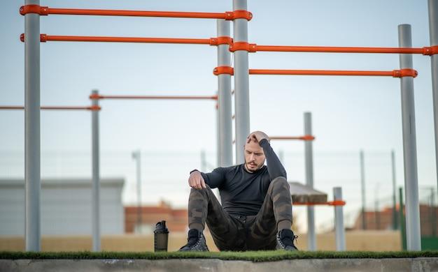 Giovane uomo ispanico seduto sull'erba nel campo sportivo che si riposa