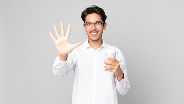 若いヒスパニック系の男性が笑顔でフレンドリーに見え、5番を示し、テイクアウトのコーヒーを持っています Premium写真