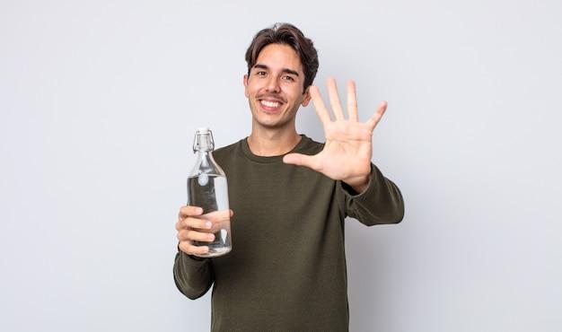 Молодой латиноамериканец улыбается и выглядит дружелюбно, показывая номер пять. концепция бутылки с водой