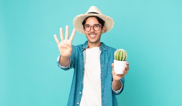 若いヒスパニック系の男性は笑顔でフレンドリーに見え、4番を示し、サボテンを持っています