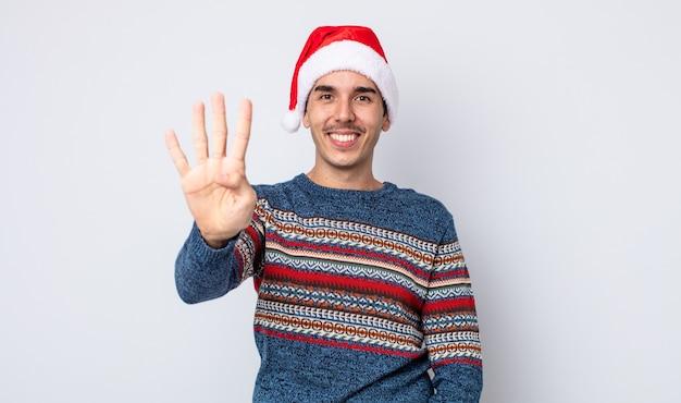 Молодой латиноамериканец улыбается и выглядит дружелюбно, показывая номер четыре. новогодняя и рождественская концепция