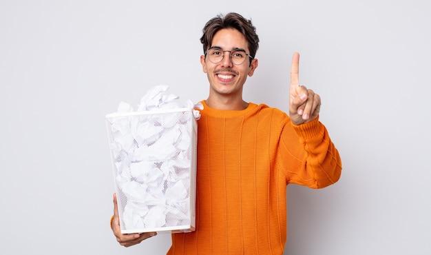 Молодой латиноамериканец улыбается и выглядит дружелюбно, показывая номер один. бумажные шары мусор концепция