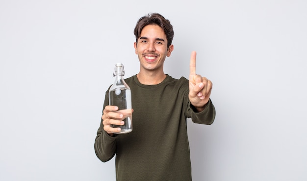 Молодой латиноамериканец улыбается и выглядит дружелюбно, показывая номер один. концепция бутылки с водой