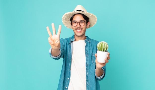 若いヒスパニック系の男性は笑顔でフレンドリーに見え、3番目を示し、サボテンを持っています