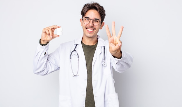 Молодой латиноамериканец улыбается и выглядит дружелюбно, показывая номер три. врач с концепцией бутылки таблетки