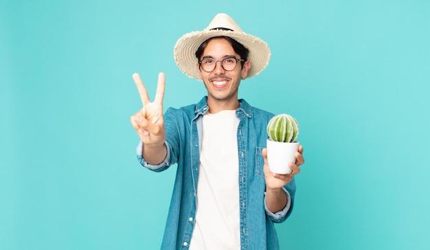 若いヒスパニック系の男性は笑顔でフレンドリーに見え、2番目を示し、サボテンを持っています