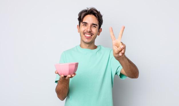 Молодой латиноамериканец улыбается и выглядит дружелюбно, показывая номер два. концепция пустой чаши
