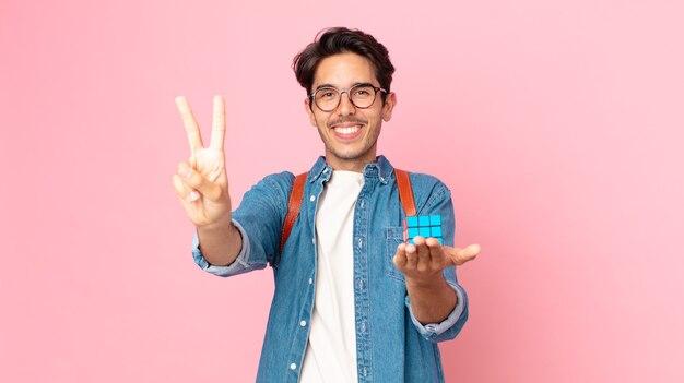 Молодой латиноамериканец улыбается и выглядит дружелюбно, показывая номер два с игрой на разведку