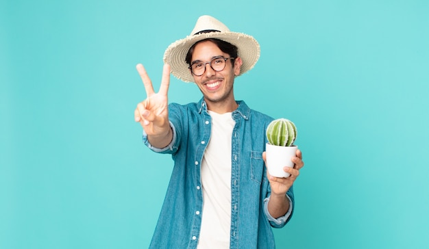若いヒスパニック系の男性は笑顔で幸せそうに見え、勝利または平和を身振りで示し、サボテンを持っています