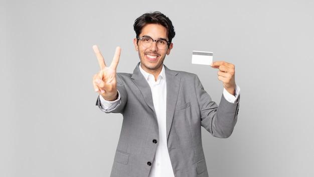 웃고 행복해 보이는 젊은 히스패닉 남자, 승리 또는 평화를 몸짓으로 표시하고 신용 카드를 들고