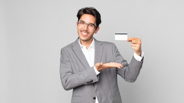 젊은 히스패닉 남자는 즐겁게 웃고 행복하고 개념을 보여주고 신용 카드를 들고 있습니다.