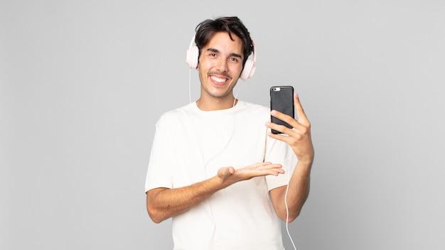 陽気な笑顔、幸せな気持ち、ヘッドフォンとスマートフォンでコンセプトを示す若いヒスパニック系男性