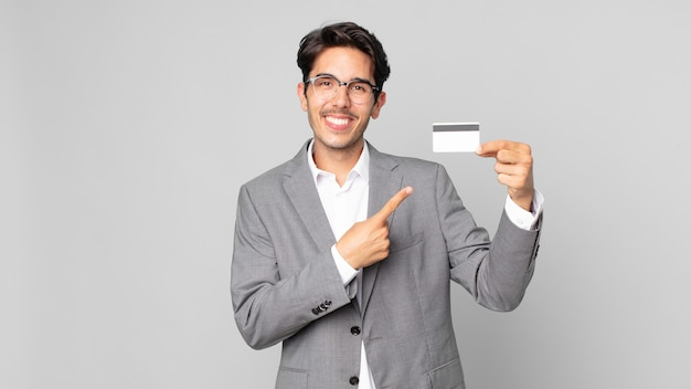 Young hispanic man smiling cheerfully, feeling happy and pointing to the side and holding a credit card