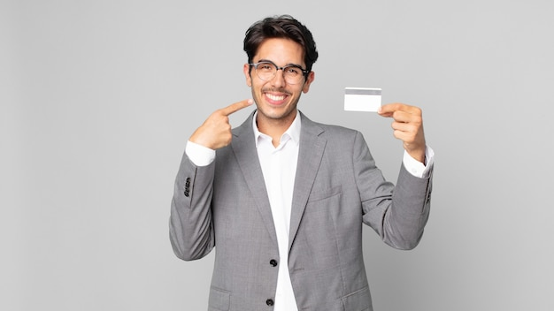 Young hispanic man smiling confidently pointing to own broad smile and holding a credit card
