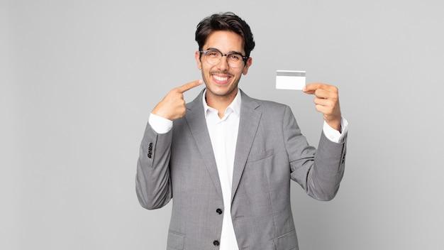 자신의 넓은 미소를 가리키며 신용 카드를 들고 자신 있게 웃고 있는 젊은 히스패닉 남자